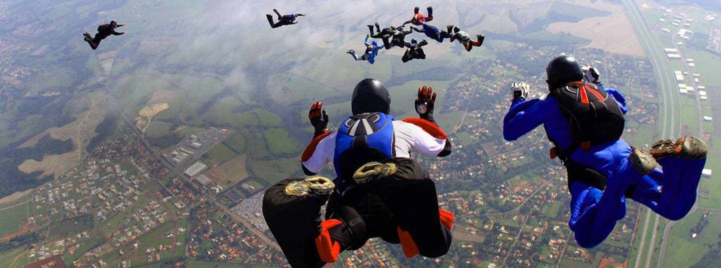 An aerial view of sixteen skydivers free-falling above a rural landscape.