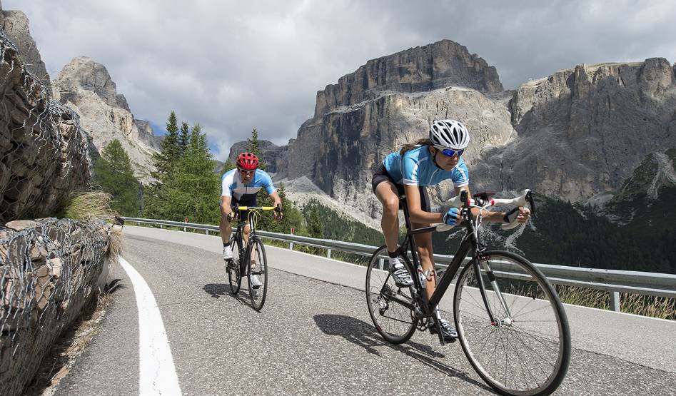Two cyclists ride on a curving mountain road; rocky outcroppings in the background.
