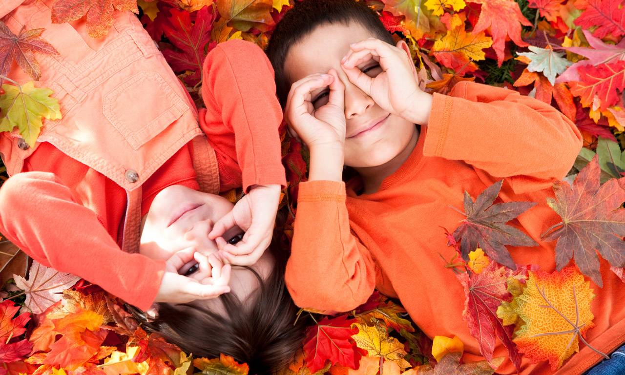 Two children dressed in orange color lying on the ground with lots maple leaves.