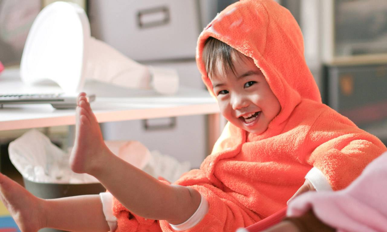 A child dressed in orange and smiling at the camera.