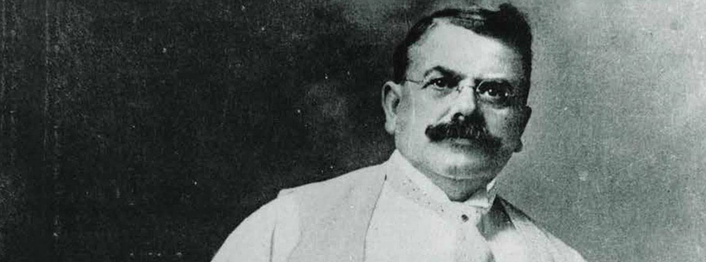 Schwarzweißaufnahme von Wallace C. Abbott.  Er hat dunkles Haar und einen kräftigen dunklen Schnurrbart, er trägt eine Brille und ein weißes Hemd, eine Weste und Krawatte.
