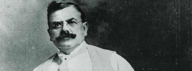 Photo en noir et blanc de Wallace C. Abbott.  Ses cheveux sont courts et foncés; il arbore une moustache fournie, puis porte une chemise blanche, un costume et une cravate.