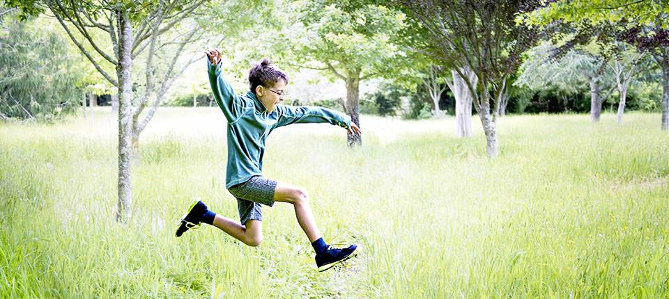 A child skips through the grass, a gaping smile upon his face.