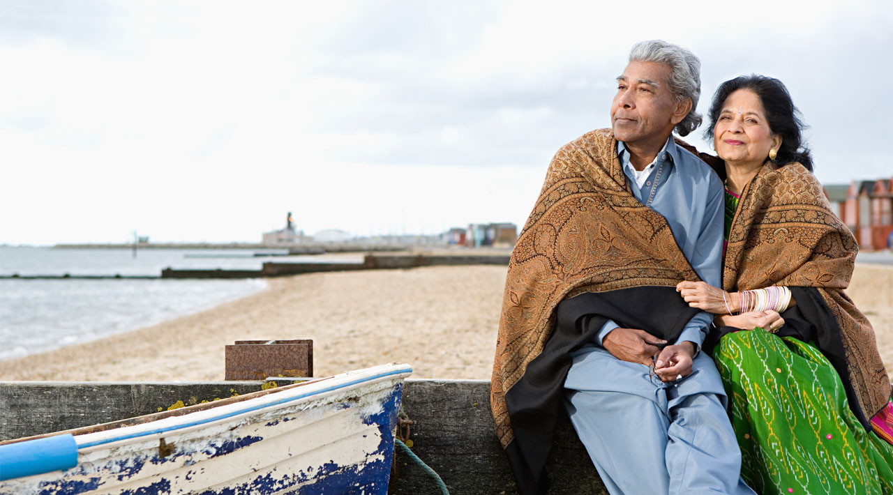 An older Indian couple sit on the beach, wrapped in a blanket staring off into the distance.