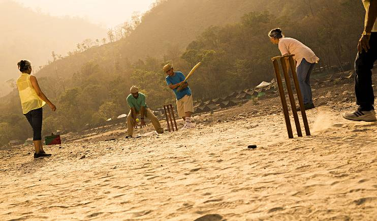 A group of active adults play an impromptu game of cricket in the setting sun.