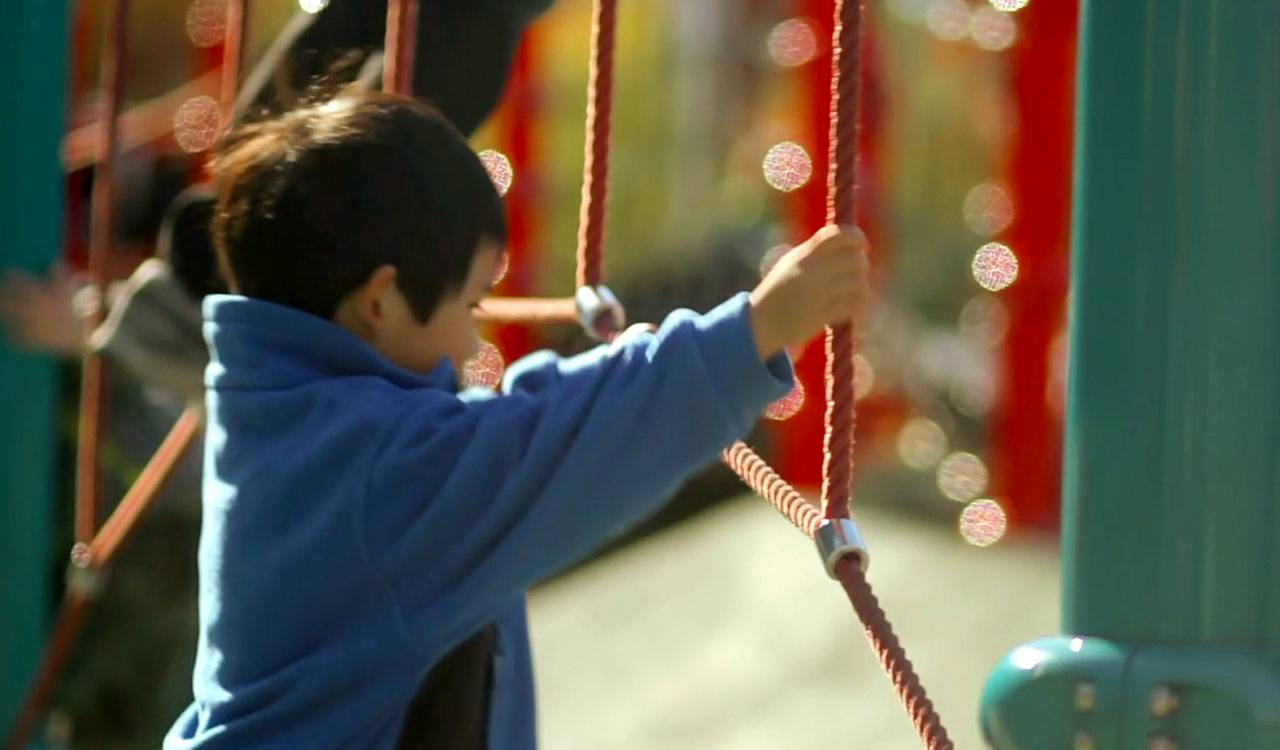 A small dark-haired boy wearing a warm blue sweater grips rope in a colorful playground.
