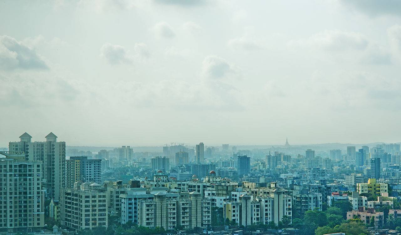 A landscape view of residential buildings enveloped in a bluish haze.