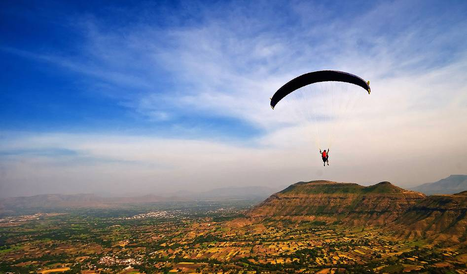 A person parachutes high above a rural landscape.