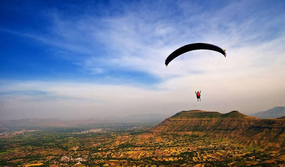 A person parachutes high above a rural landscape.