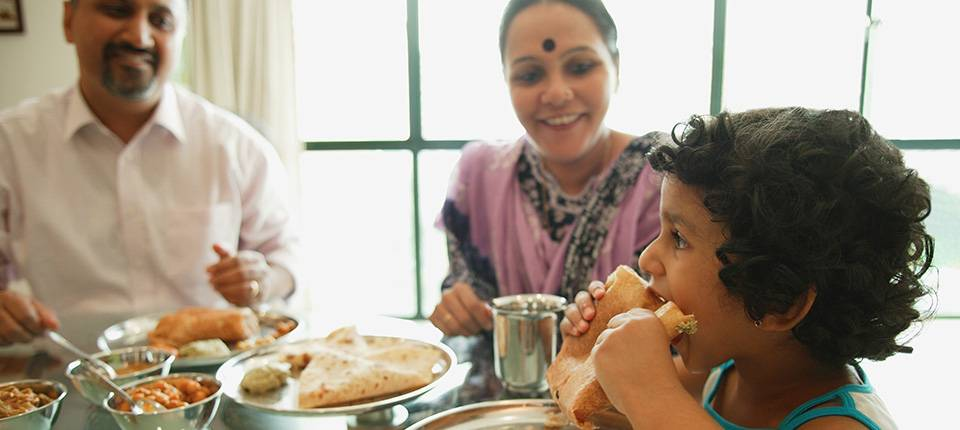 A young girl bites into a large sandwich while her parents look on from the dinner table.