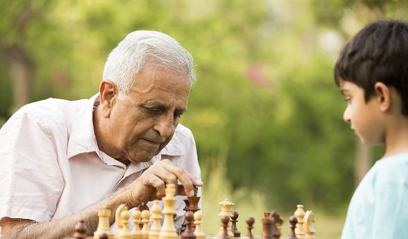 An elderly man and a young boy play a game of chess outdoors.