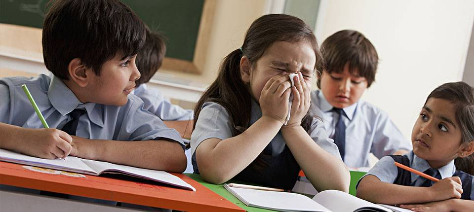 A uniformed school aged girl sneezes into a handkerchief while her classmates look on.