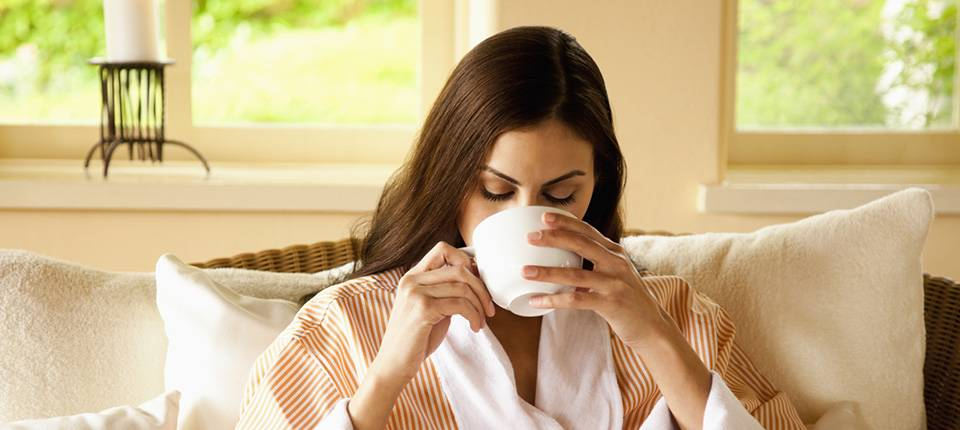 A robed woman sips from a tea cup while relaxed on a plush sofa in a sunlit room.