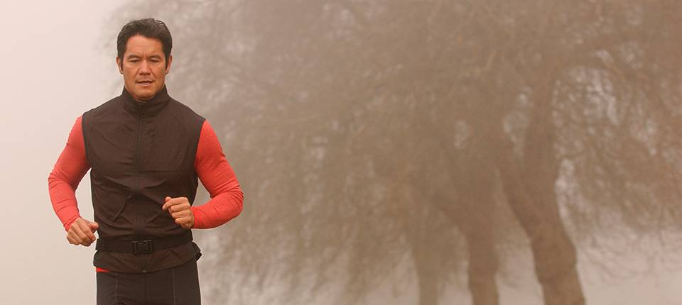 A man wearing a black vest and red shirt goes for a morning run in a foggy park.