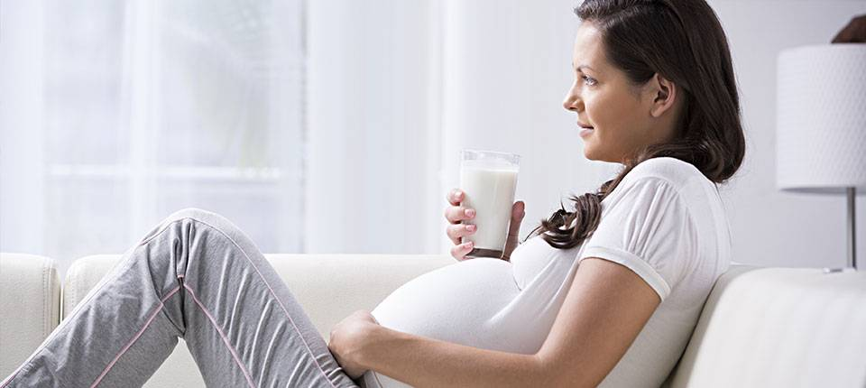 A young pregnant woman dressed in white lounges on a white couch while holding a beverage on her belly.
