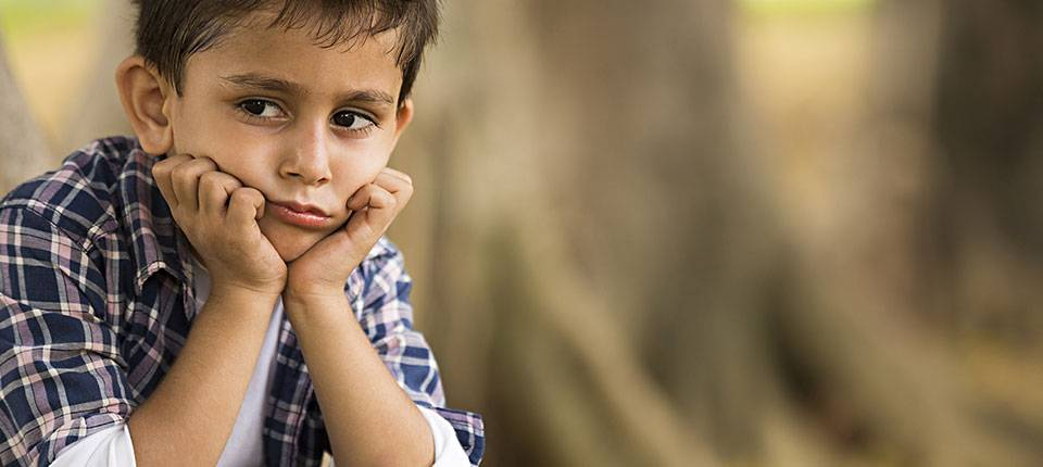 A seated boy in a plaid shirt holds his head in his hands with a look of discomfort on his face.