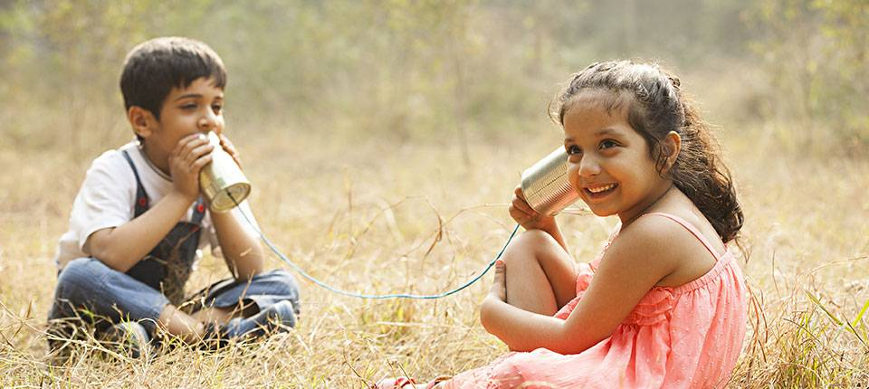 Two small Indian children seated in a field, playing telephone with two cans connected by a string.