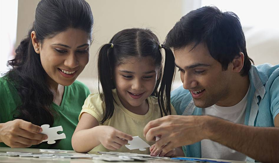 Young parents and their child work to complete a puzzle.