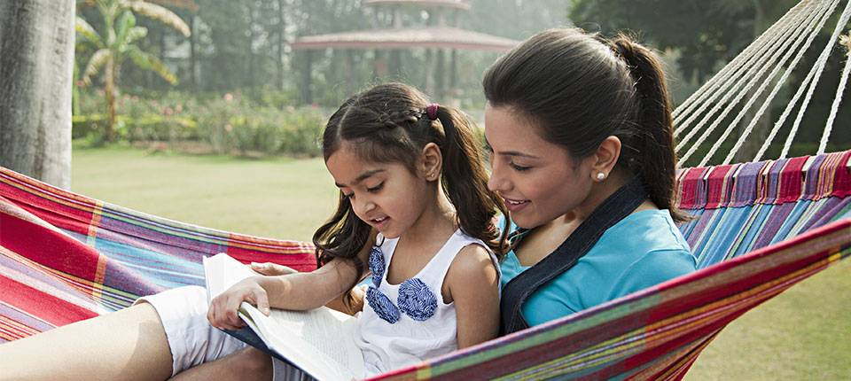 A woman sites in a colorful hammock, with a child on her lap, the two of them reading from a book.