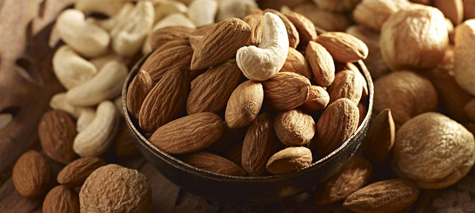 A bowl of almonds, topped with a cashew, sitting atop a bed of mixed nuts.