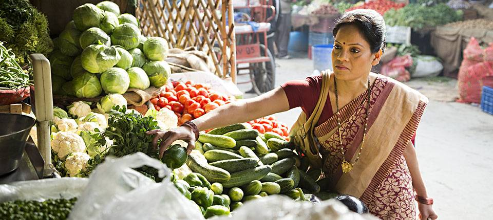 A woman in a sari picks over fruits and vegetables in the sunny backdrop of a farmer's market.