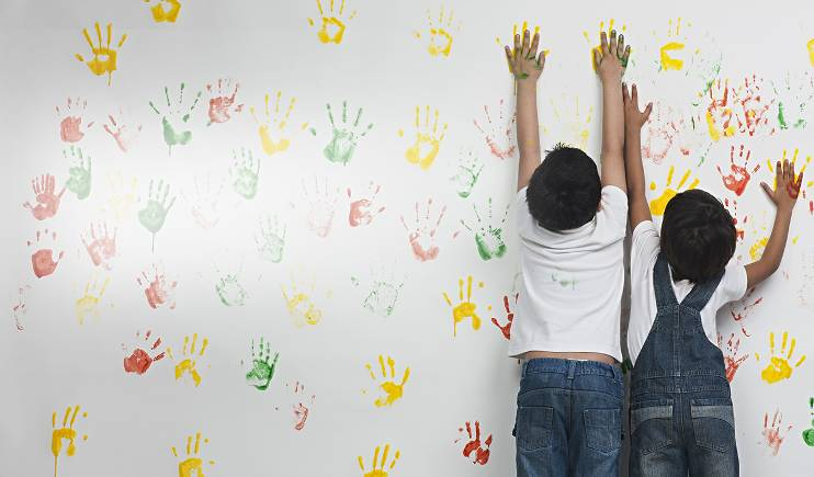 Two young Indian children, leave paint handprints in red and yellow on a white wall.