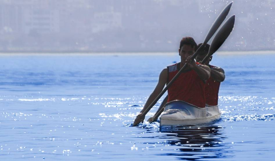 Two young men kayak in unison on a body of calm water in the bright sunlight.