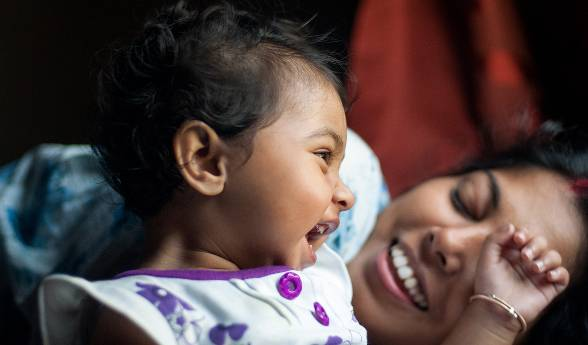 A seated toddler and her reclining mother laugh together.