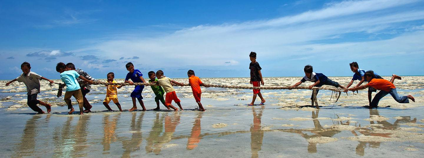 Under a blue sky, young Indian boys in bright clothing play tug of war in shallow water.