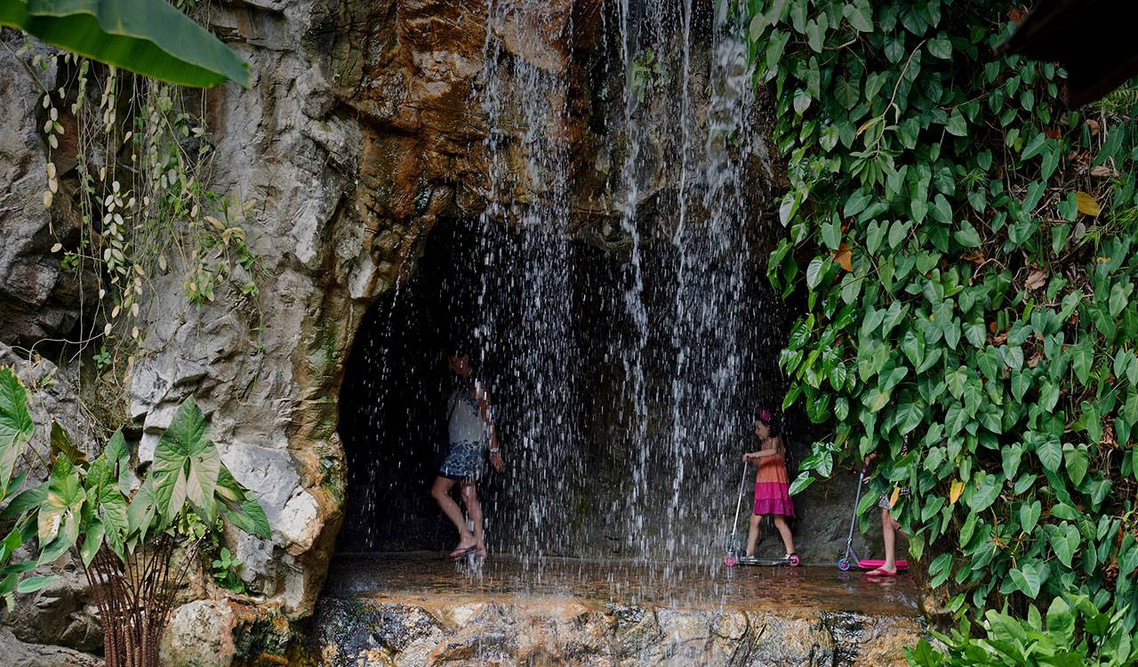 Young girls with scooters play behind a waterfall.