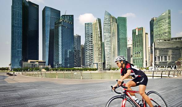 A woman on a triatholon bike speeds across the boardwalk in front of a modern city scape