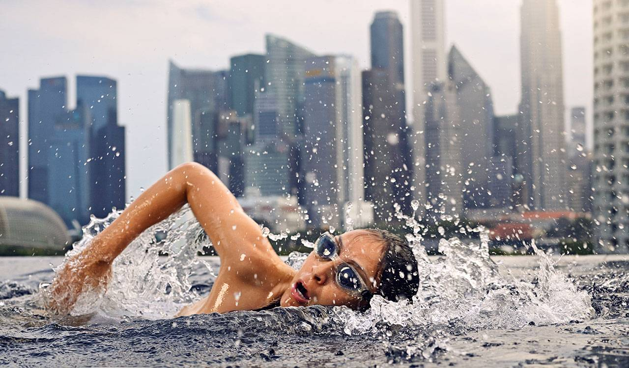 A woman wearing goggles takes a breath while swimming freestyle, the skyline of Singapore visible in the background.