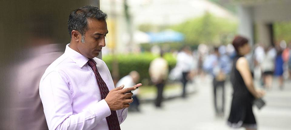 A young well-dressed Indian man checks his phone outside.