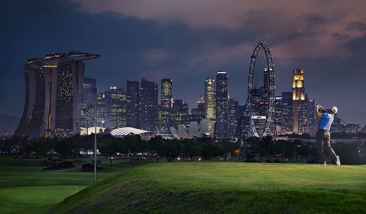 A man finishes his backswing on a lighted golf course with a night time city scape in the background.