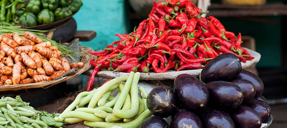Purple eggplant, green beans and red chili peppers in a market stall.