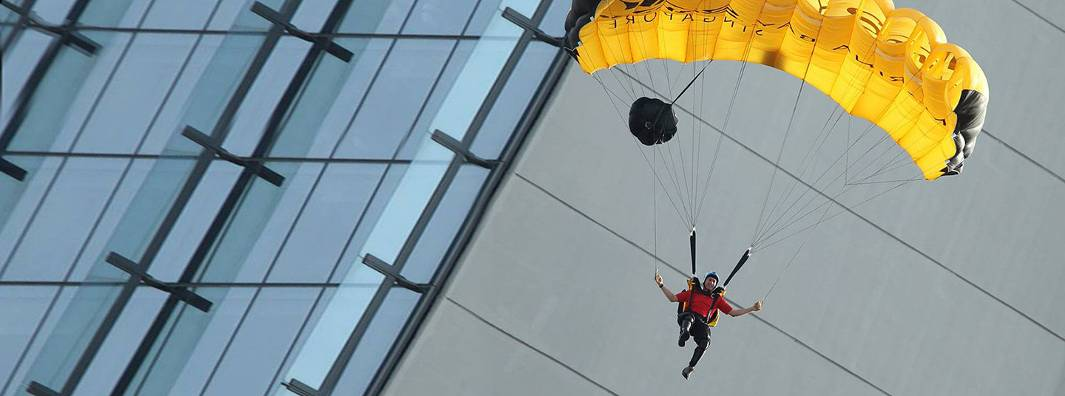 A skydiver wearing a red shirt maneuvers his yellow parachute near a modern building.