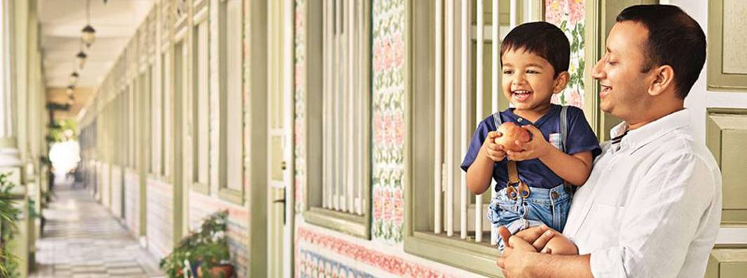 A man standing in a long outdoor corridor, holds a young boy who is gripping an apple in his hands.
