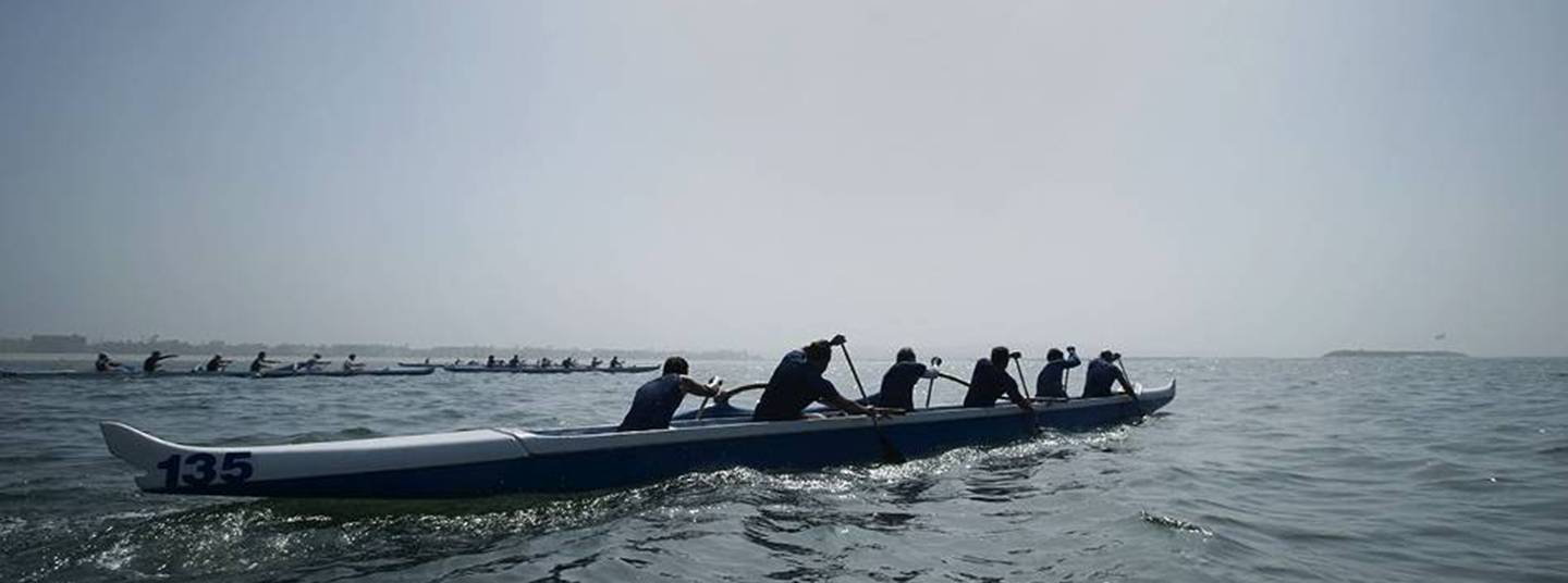 Six athletes compete in a canoe sprint on a calm, bright lake.