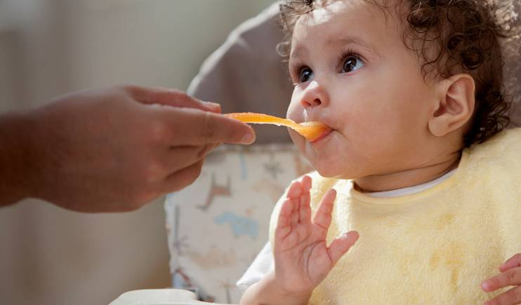 A person's hand spoon-feeding a baby in a yellow bib.