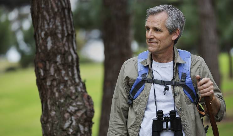 A gray-haired man looks to his right as he hikes through the woods wearing binoculars and a backpack.
