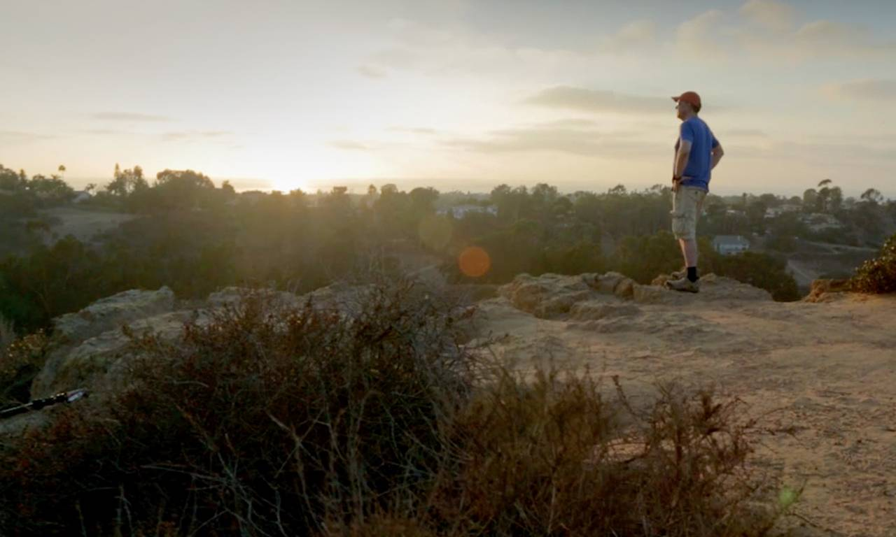 A man in a blue shirt, shorts and a cap looks off into the sunset from atop a plateau.