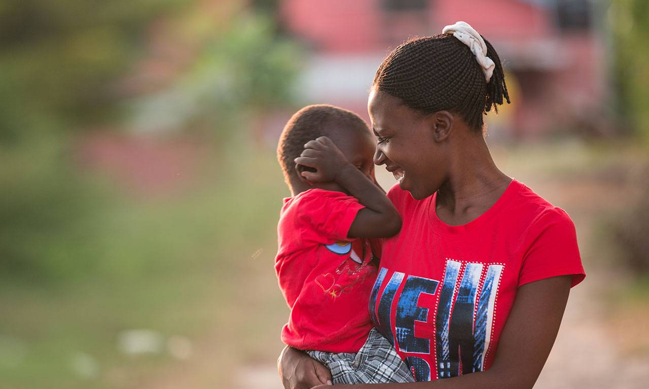 A smiling African woman holds a young child on her right shoulder.