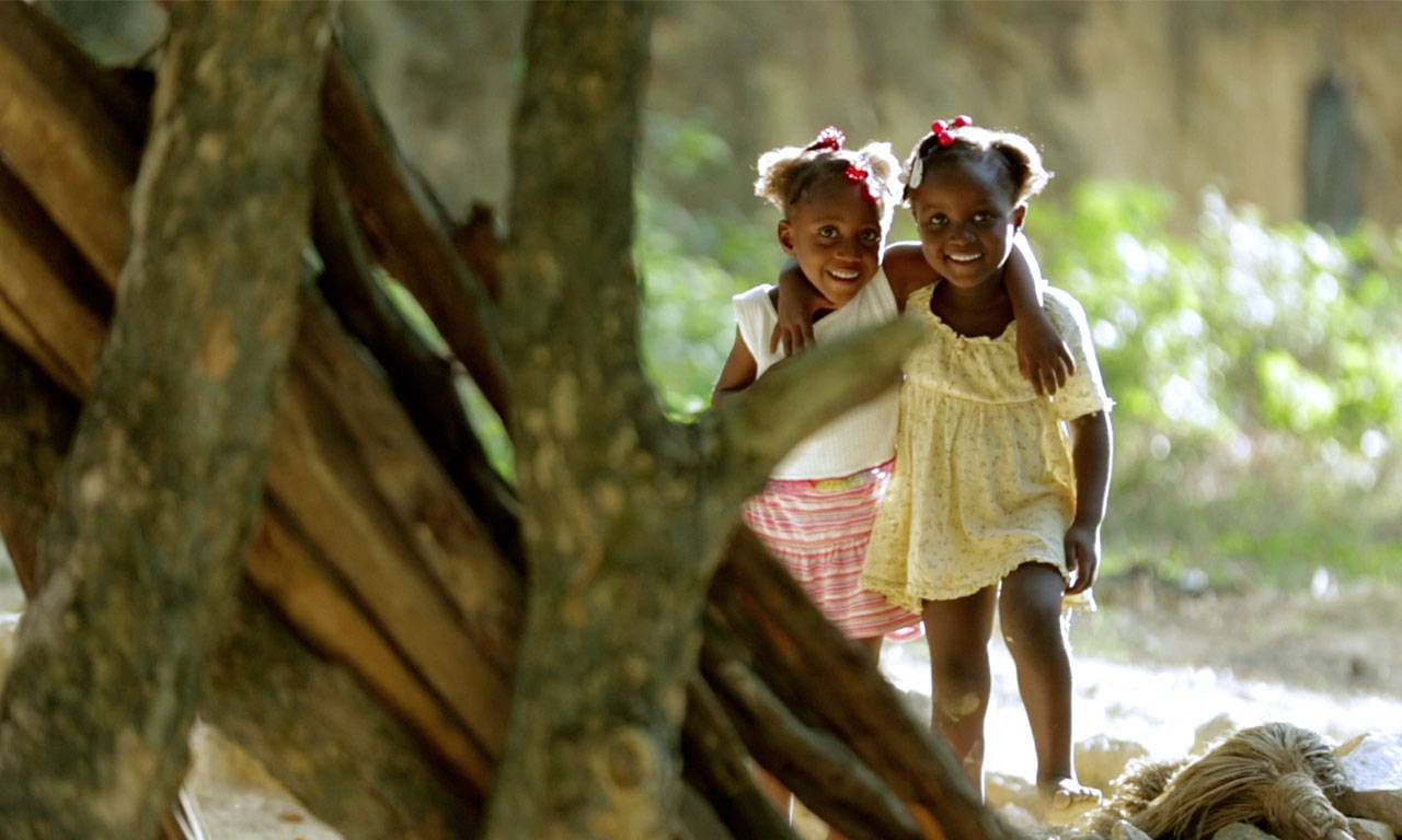 Two smiling children with arms around one another, a tree in the foreground.