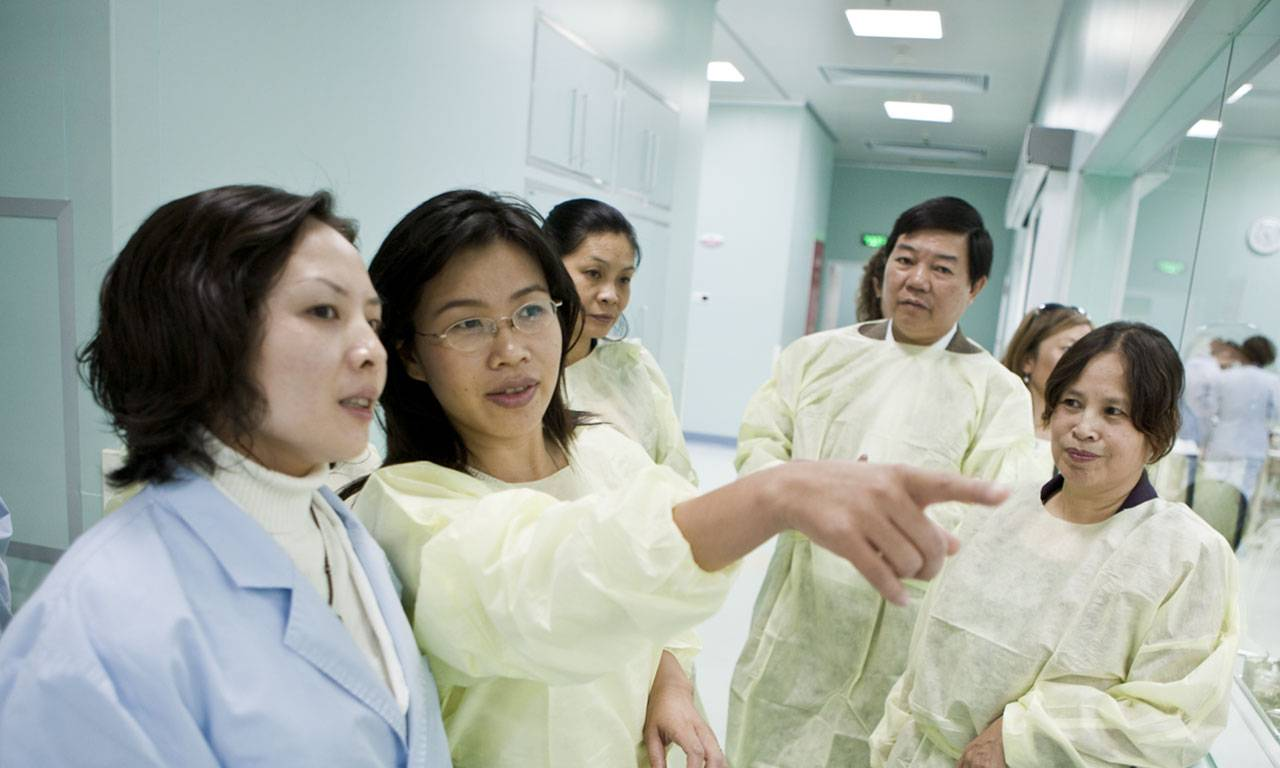 An asian woman in a lab coat points to and explains something outside of the frame to to a group of co-workers.