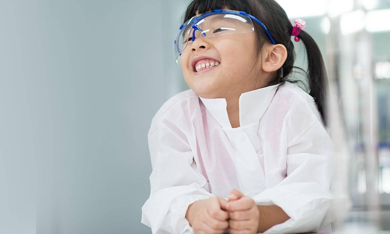 A four-year old Asian girl smiles wearing a lab coat and safety glasses in a lab.