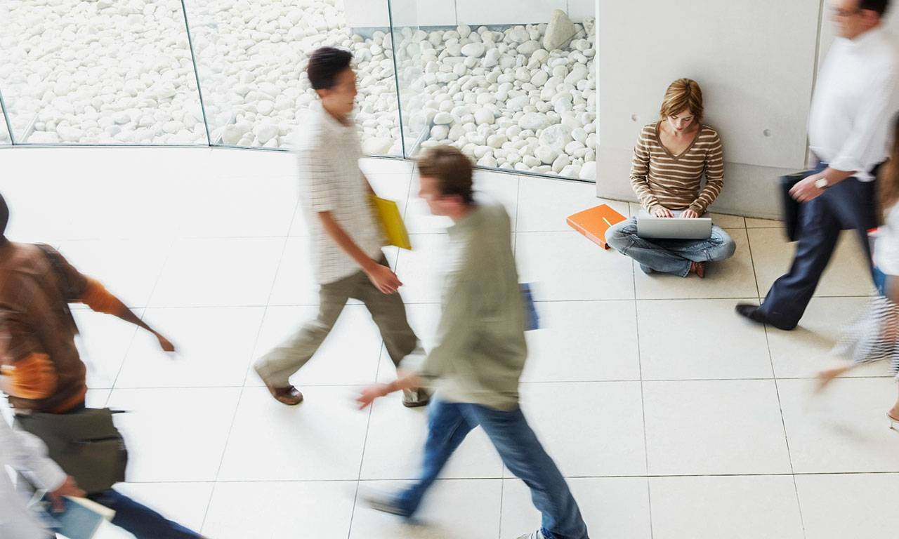Students walk by one another in a hallway in a university setting, their bodies blurred by movement.
