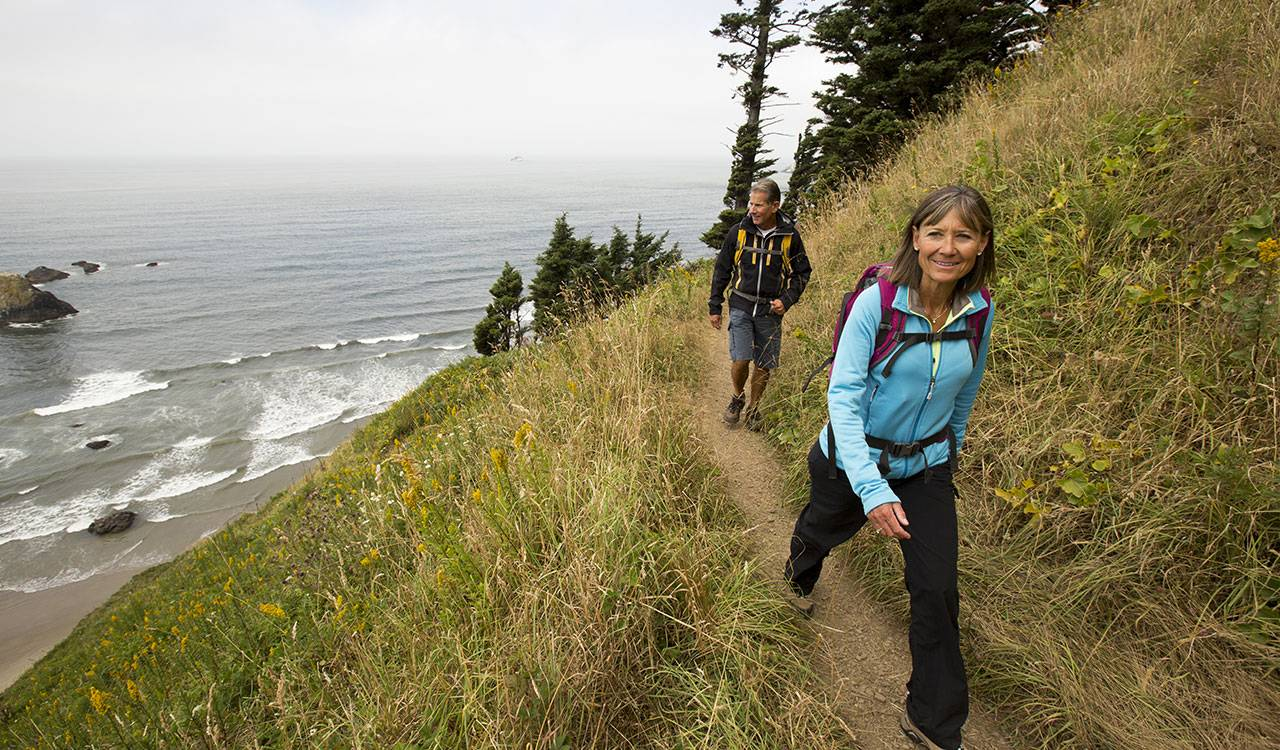 A middle-aged couple hikes along a narrow, grassy path on a hillside above the ocean. Both wear backpacks and outdoor clothing.