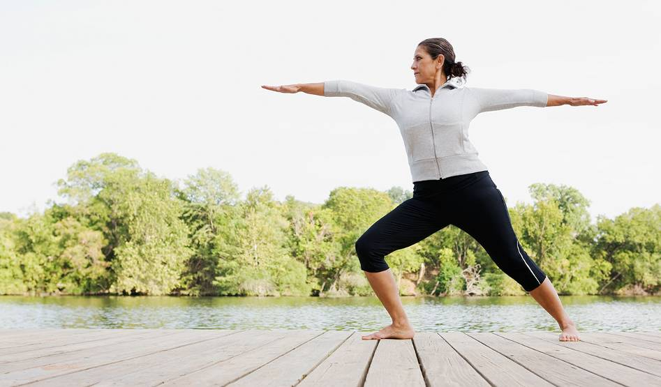 A woman stands in a yoga pose on a boardwalk by a lake.