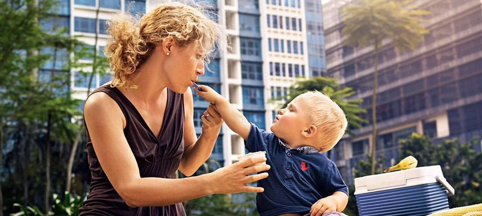 A blonde mother and her son sit outside in an urban park. He is trying to feed her yogurt from a blue spoon.