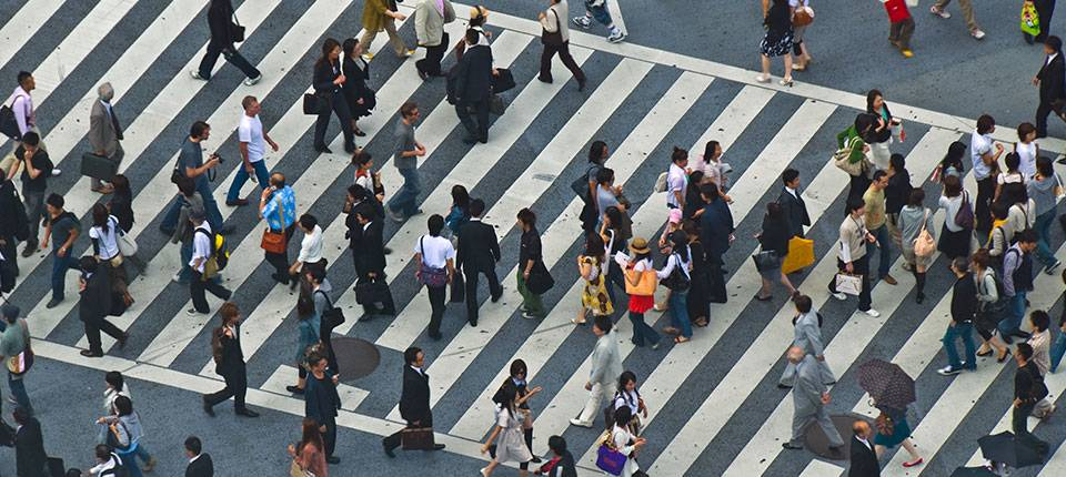 An overhead view of a crowd crossing a wide, striped cross walk.